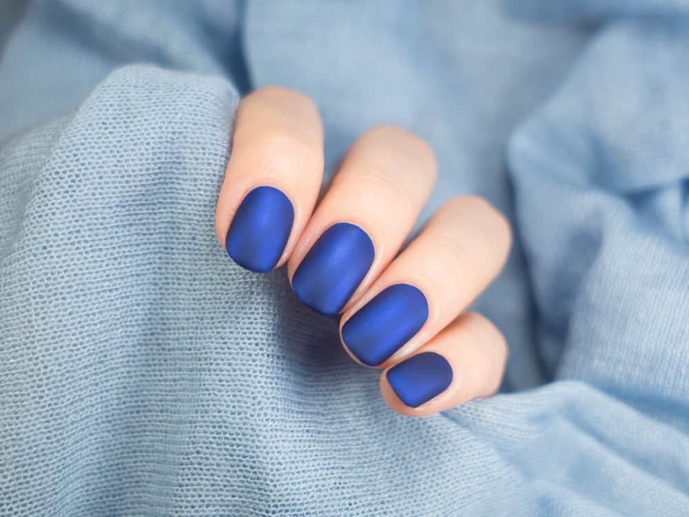 Beautiful blue matt manicure. Blue background closeup.