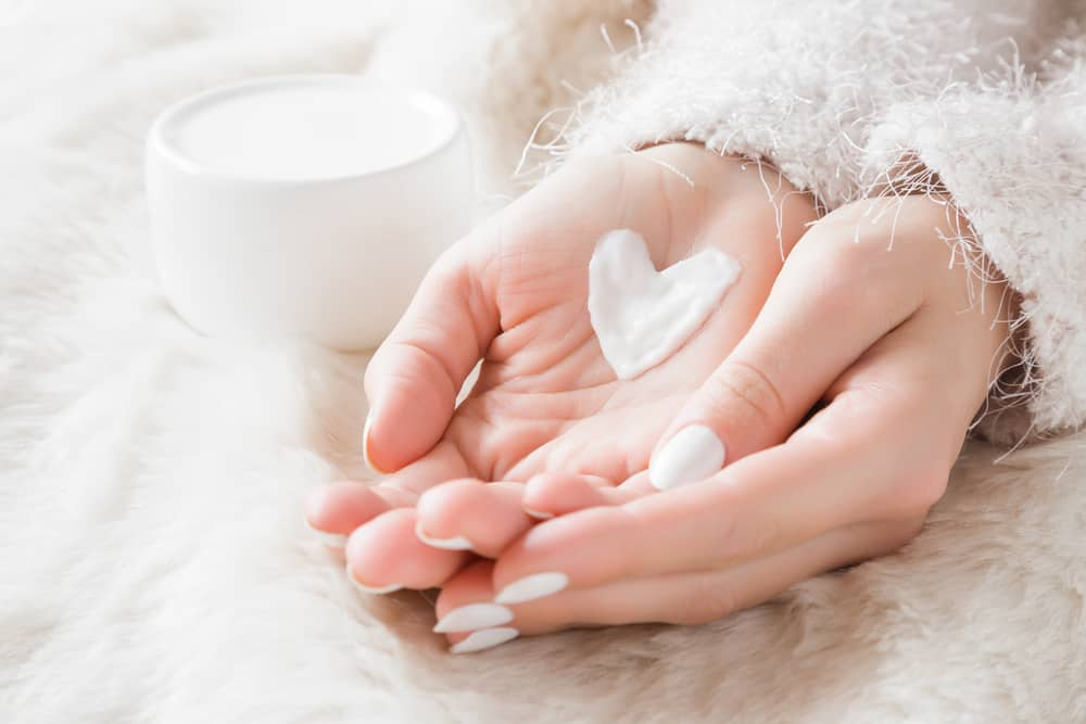 Beautiful groomed woman's hands with cream jar on the fluffy blanke