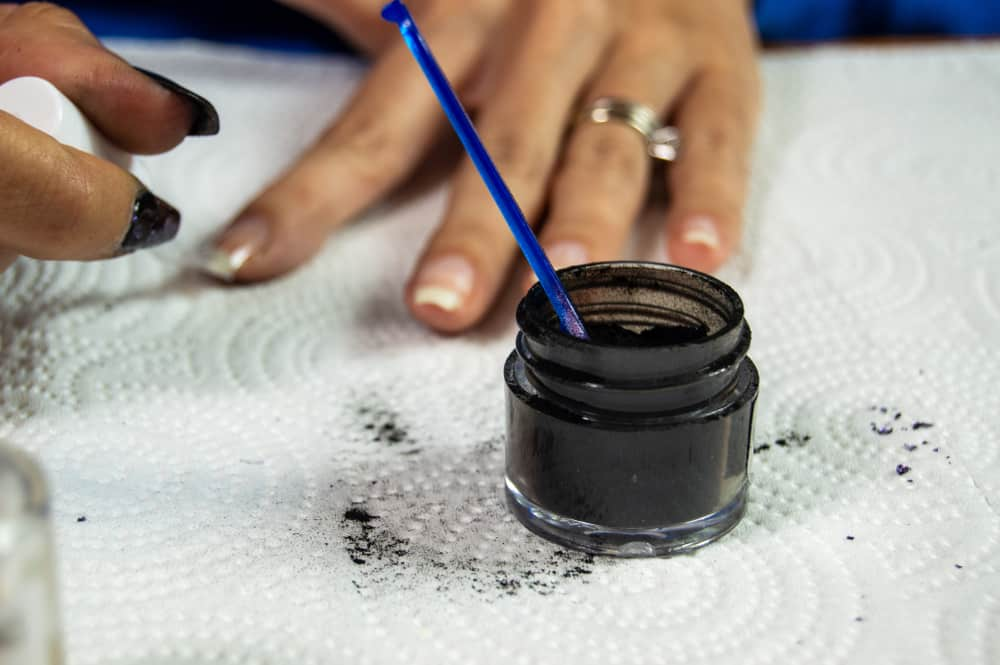 Black acrylic dip powder sitting on white paper towel