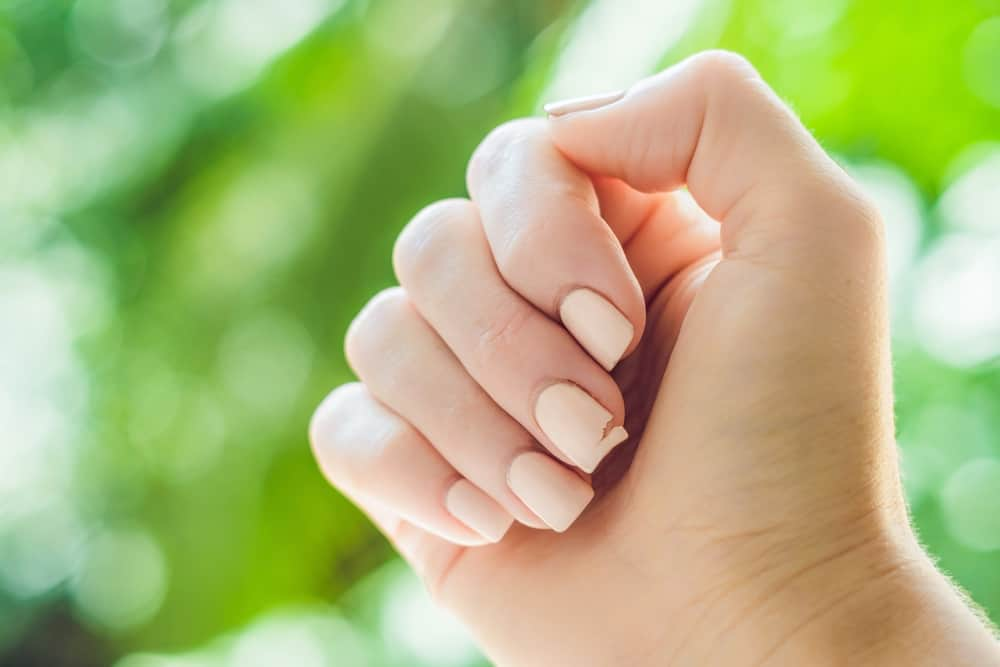 Broken nail on a woman's hand with a manicure