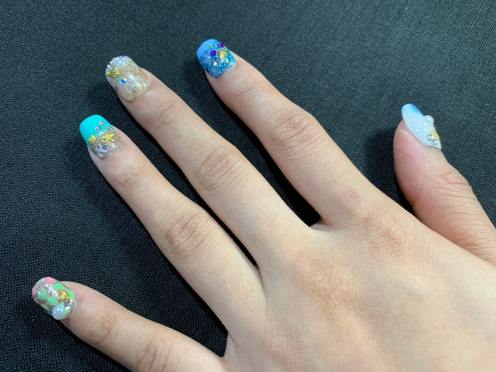 Female hand with turquoise nail design and sea stones