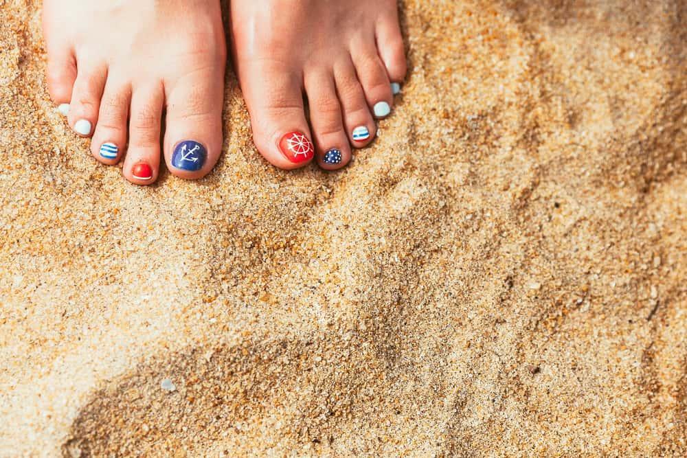 Female sea style pedicured feet on summer shore