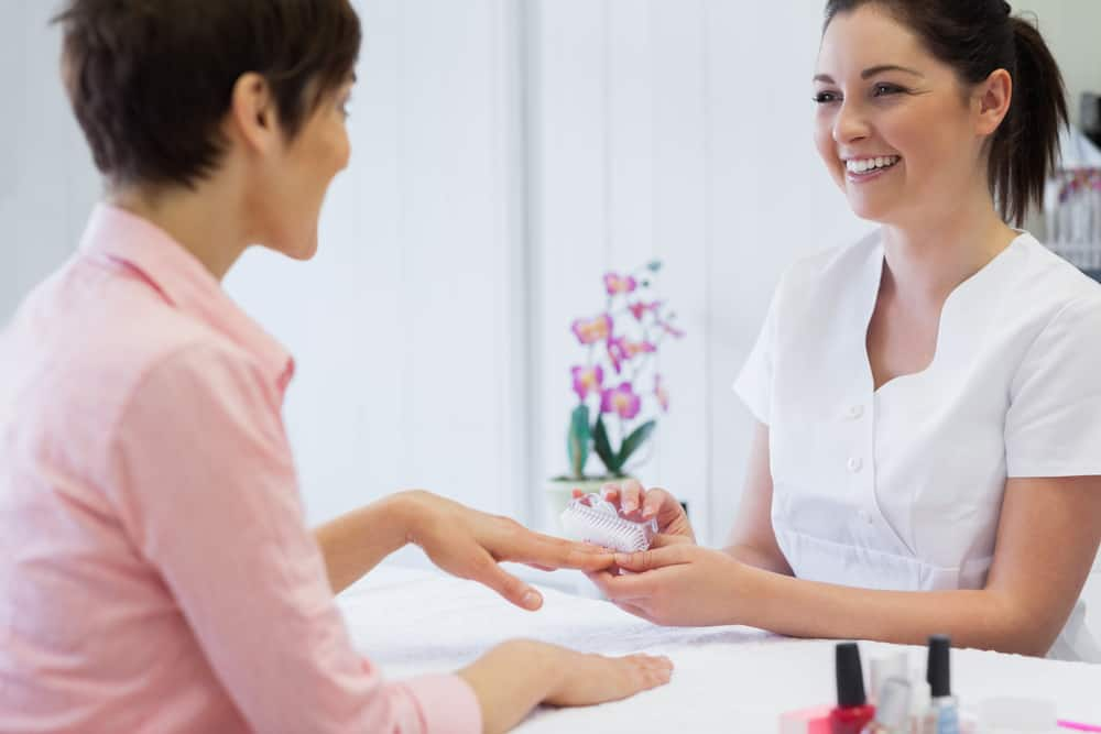 Happy young manicurist using nail brush on woman's nails