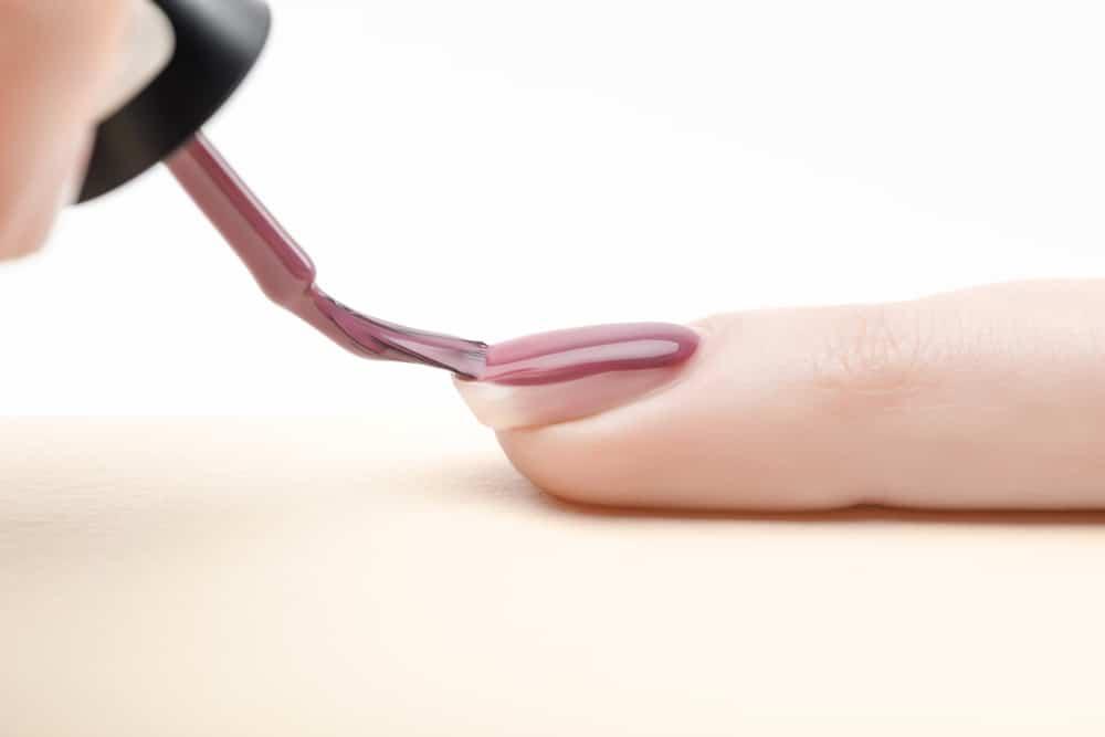 Manicurist applying purple nail polish on fingernail of woman