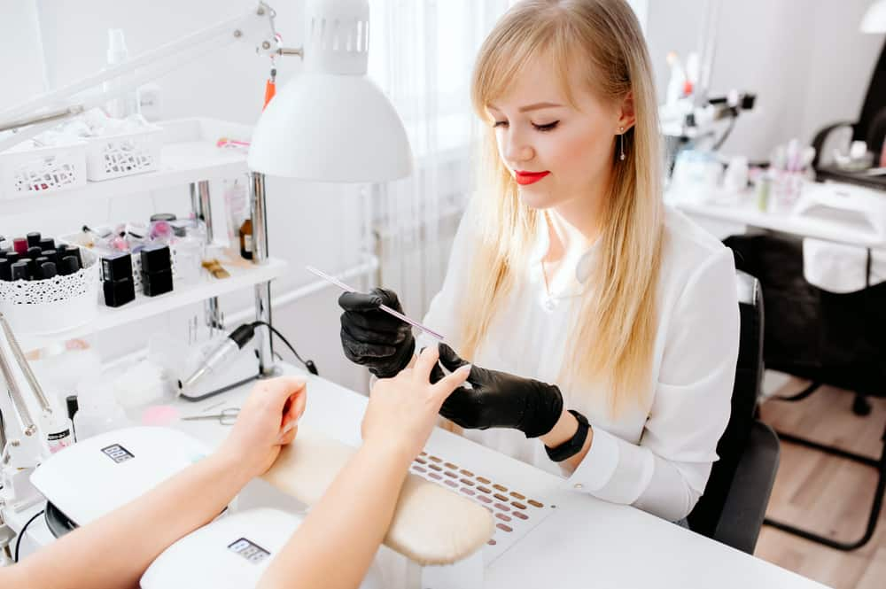 Manicurist work on a woman client hands