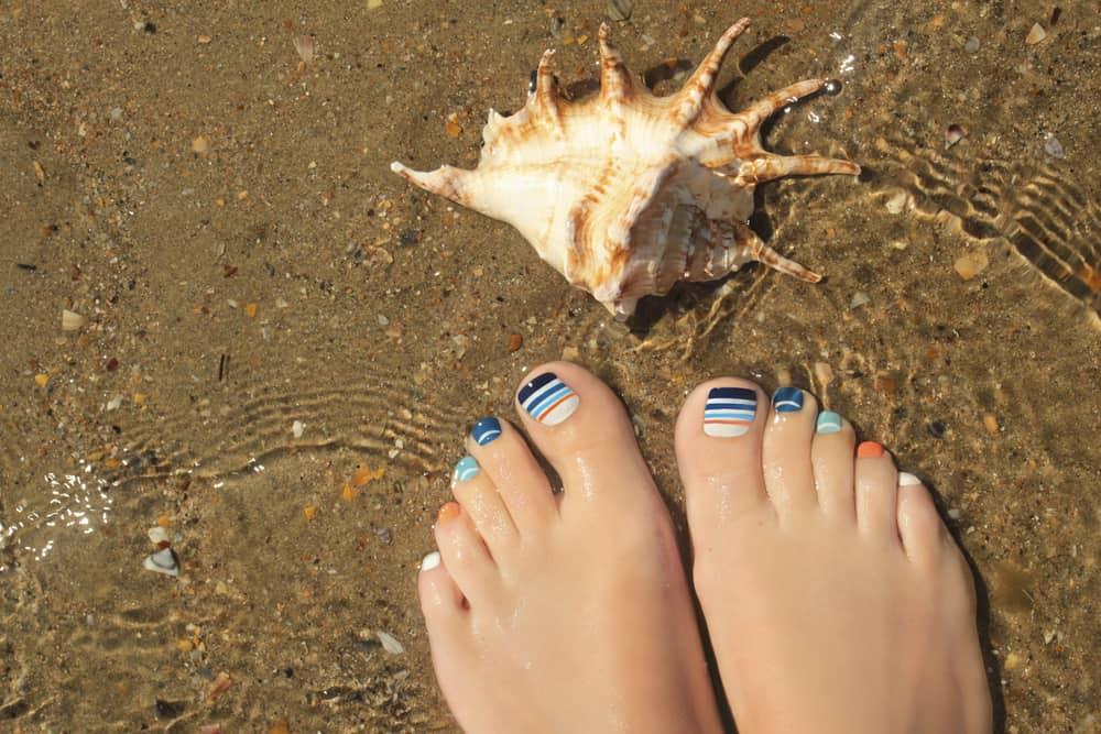 Marine striped multicolored pedicure on female nails on summer sea closeup