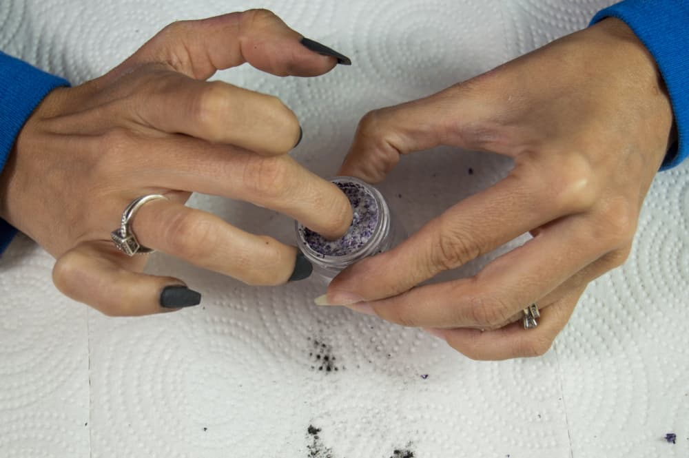 Middle finger of a Caucasian hand being dipped in sparkly dip powder