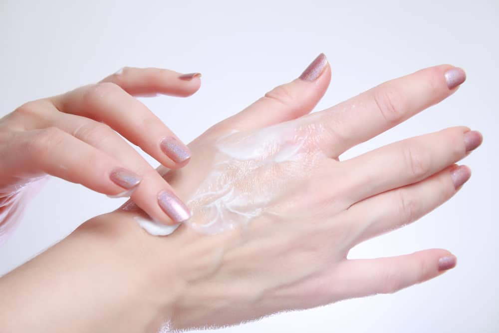Woman applying moisturizing cosmetic creams
