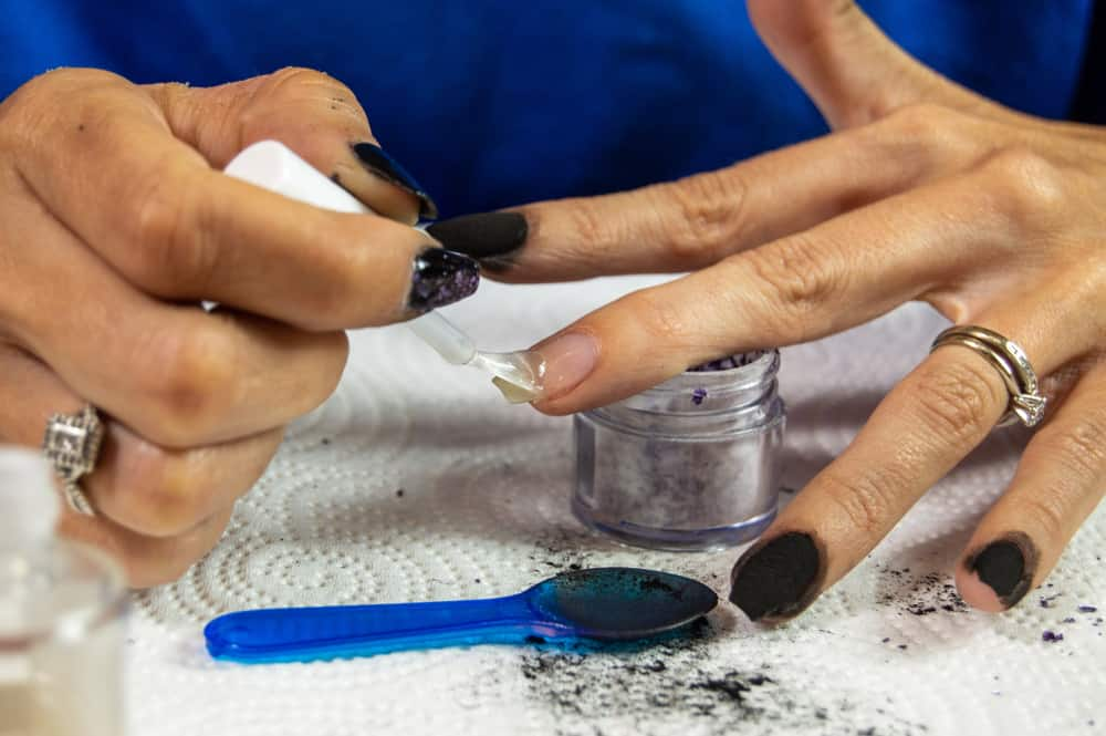 Woman putting base coat on her nails before dipping them in dip powder
