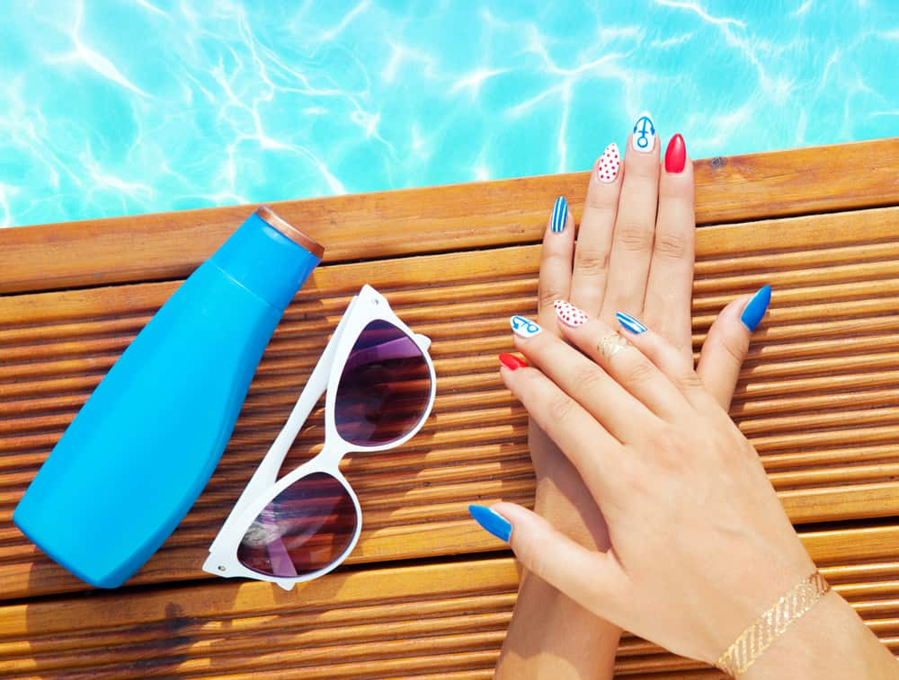 Woman with gel nails holding sunglasses