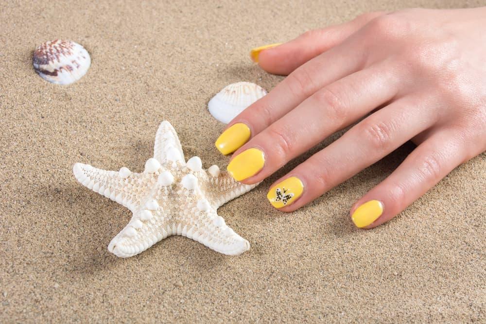 Woman with yellow nails manicure polish