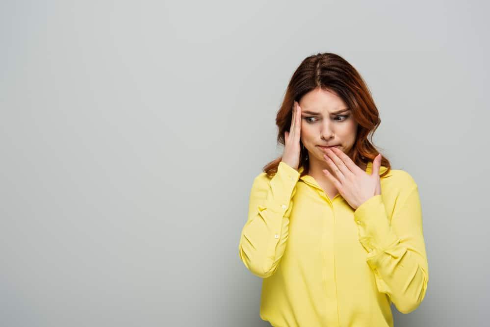 Worried woman in yellow shirt