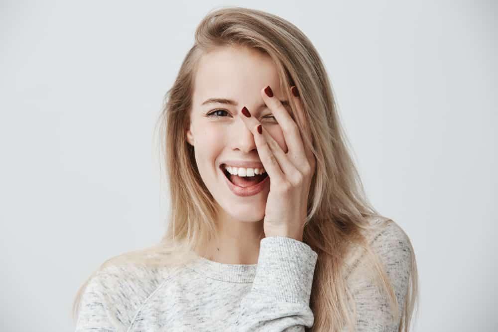woman with dark eyes, blonde long hair, happy gentle smile
