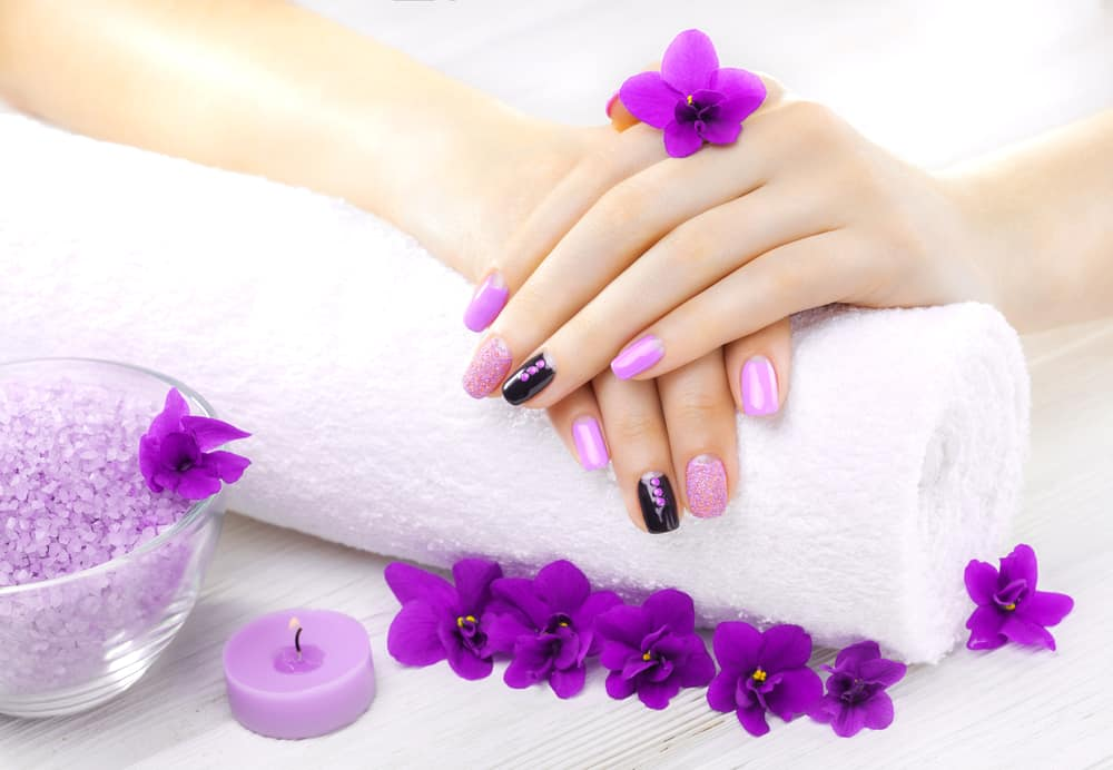 Beautiful purple manicure with violet, candle and towel