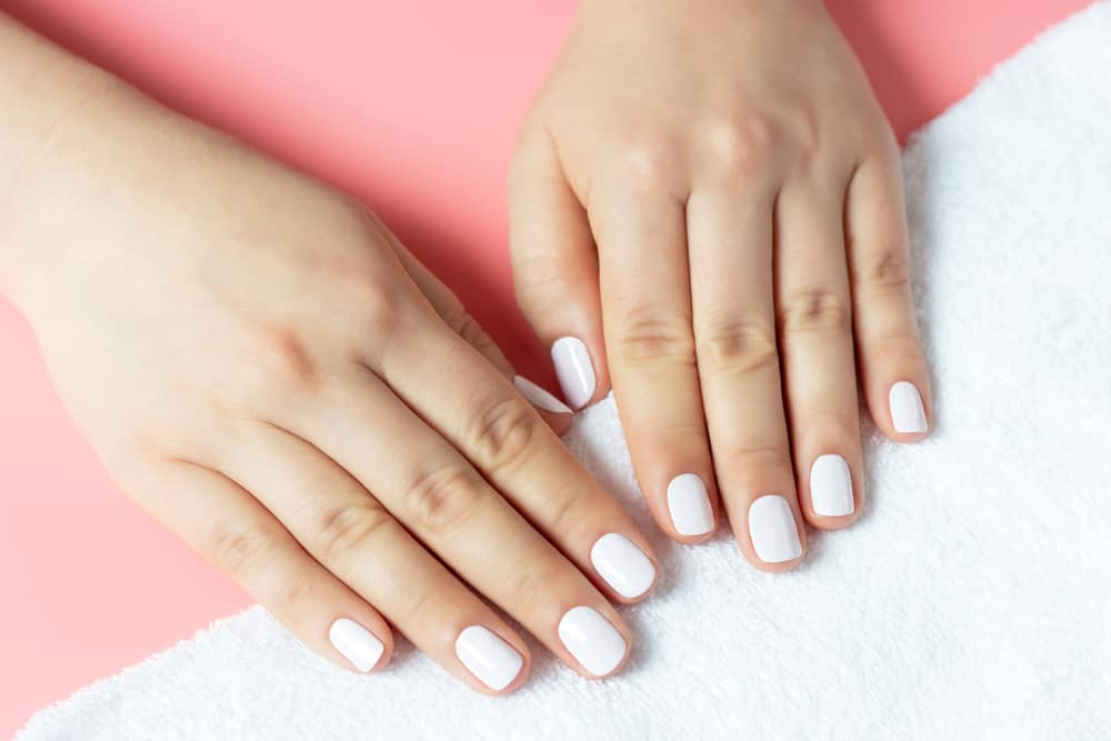Beautiful women's hands with white manicure on a pink and white background
