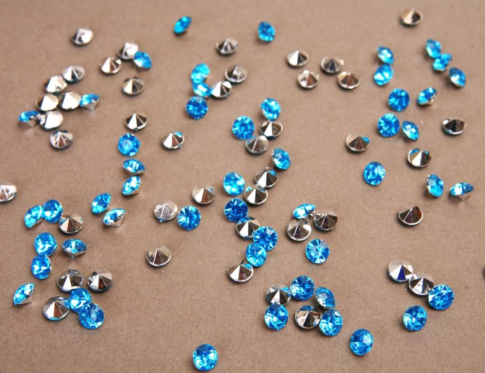 Blue shiny stones scattered on beige background