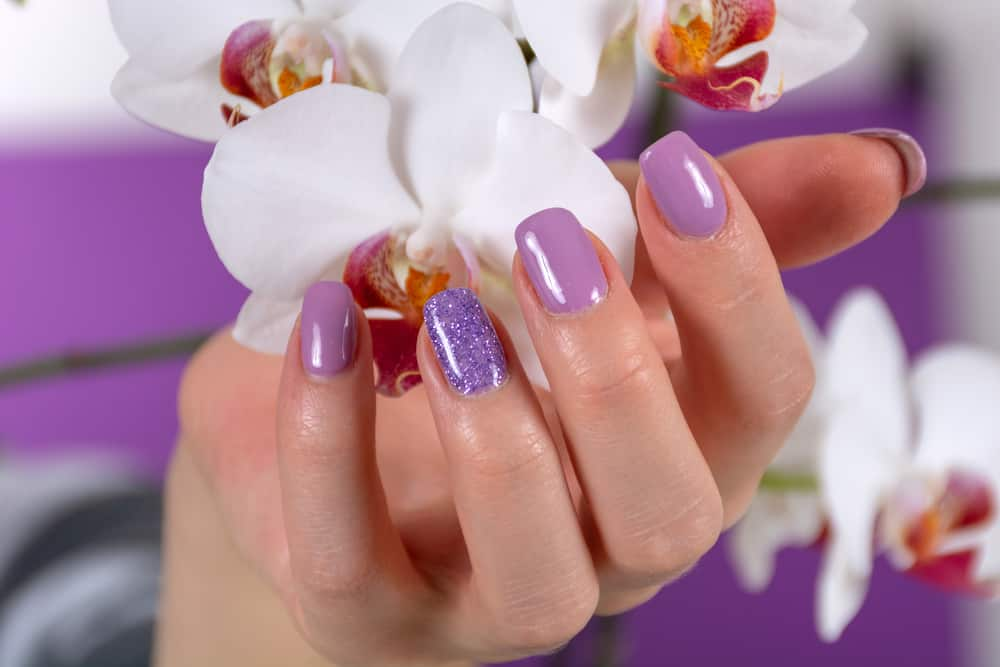 Female hand with a lilac color nails polish gel