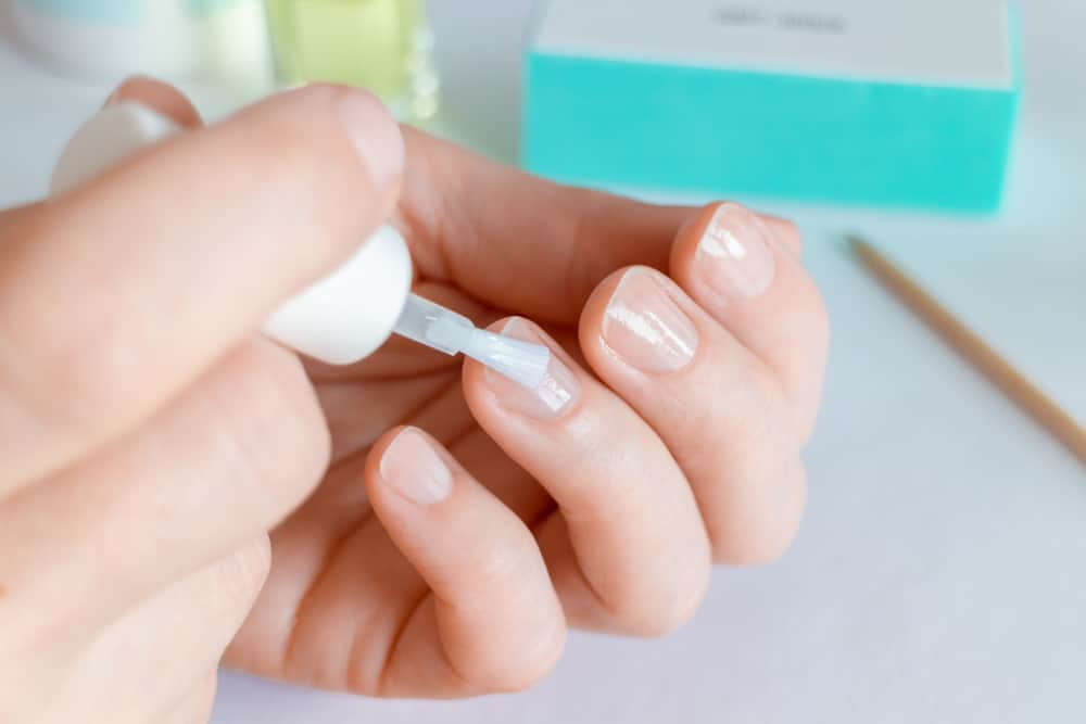 Woman doing at-home manicure, applying nail conditioner or base coat