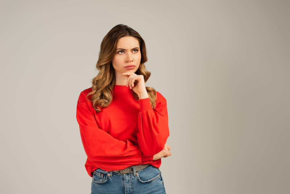 Woman in red sweatshirt looking away and thinking