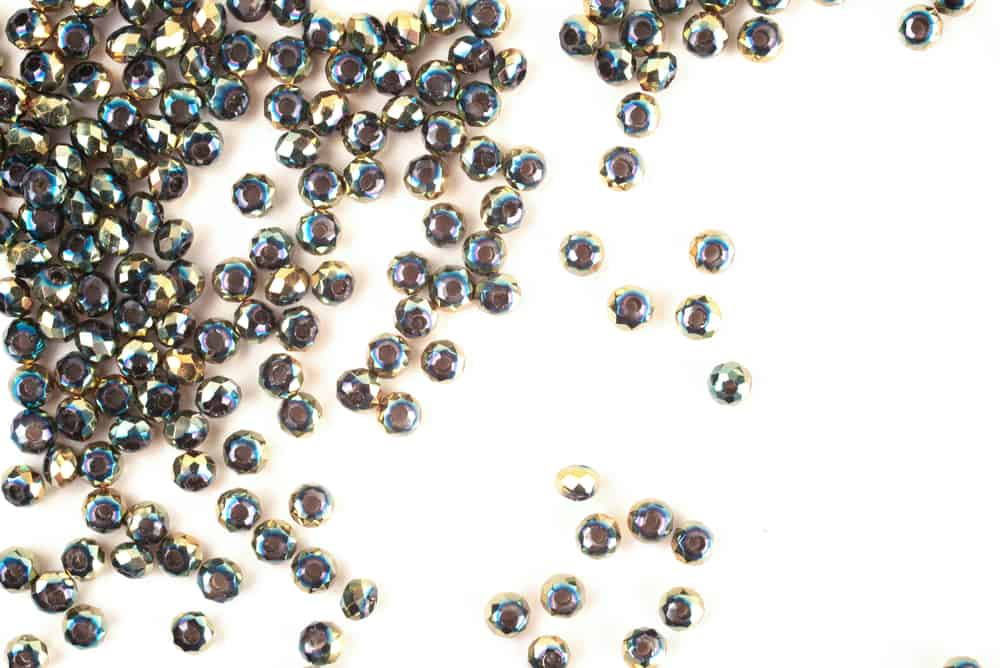 Green beads are scattered on a white background
